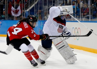 Team USA's goalie Jessie Vetter (R) plays the puck as Canada's Natalie Spooner forechecks during the first period of their women's ice hockey game at the Sochi 2014 Sochi Winter Olympics, February 12, 2014. REUTERS/Jim Young (RUSSIA - Tags: SPORT OLYMPICS SPORT ICE HOCKEY) - RTX18NV9