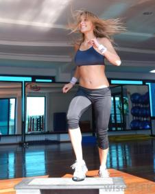 woman-doing-step-aerobics-in-gym