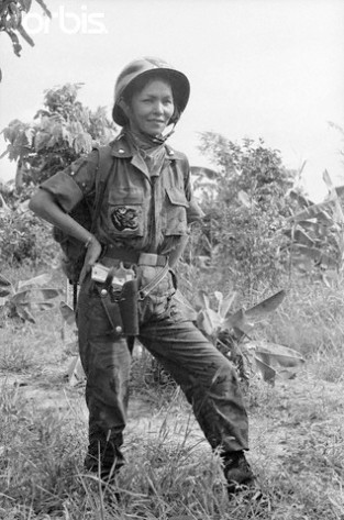 "19 Jun 1965, South Vietnam --- A pearl-handled .45 automatic on her hip, HoThi Que - ""Tiger Lady"" of the vital MeKong Delta in Suth Viet Nam watches the 44th Vietnamese Ranger Battalion march into the jungle in pursuit of Red Viet Cong Guerrillas. The Battalion - Recently awarded the US Presidential Citation for Extraordinary Hero- is under the command of Major de Van Dan, who is her husband. --- Image by © Bettmann/CORBIS"