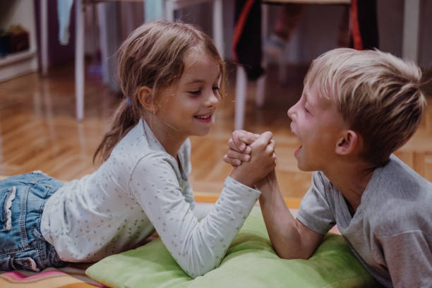 Two cute kids lying down and arm wrestling