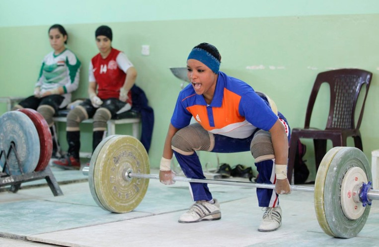 An Iraqi weightlifter shouts as she lifts a loaded barbell during training session at a gym in Sadr city in Baghdad