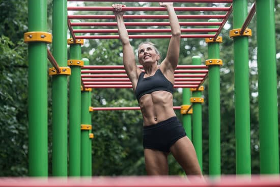 girl doing exercises on the horizontal bar. The woman is engaged in workout